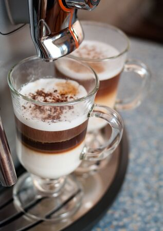 capuccino: Two glasses fileed with capuccino in cofee machine Stock Photo