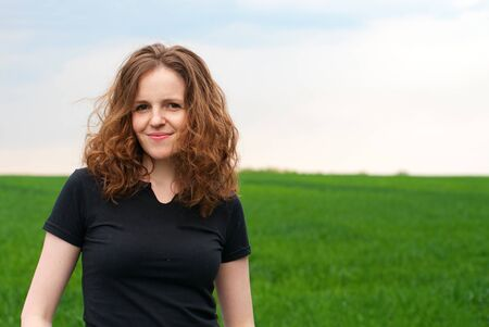 Beautiful redhead curly woman on the green field Stock Photo - 9516627