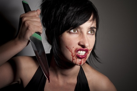 Crazy cannibal woman with blood on her face and knife in hands photo