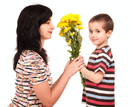 naughty woman: Little boy gives yellow flowers to his mom isolated on white Stock Photo
