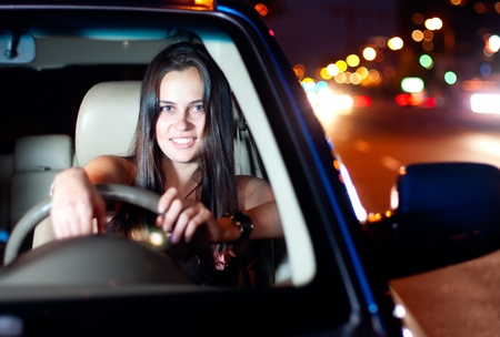 Young smiling woman driving car in the night city