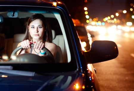 Young asian woman driving car in the night city photo
