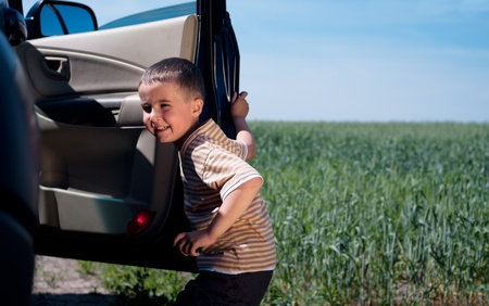 Little boy leaving the car outdoors photo