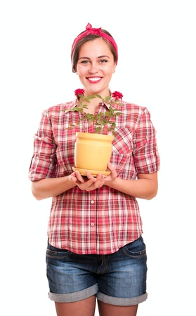 Happy housewife in kerchief with rose flower pot isolated on white photo