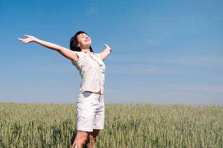 Happy woman enjoy sun on the wheat field Stock Photo