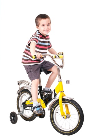 Happy little boy on bike isolated on white photo
