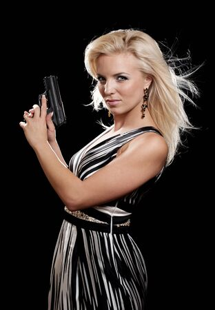 Portrait of blonde woman in evening dress holding gun isolated on black photo