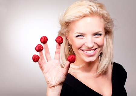 Portrait of blonde woman stick strawberry on fingers photo