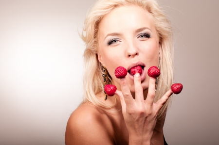 Portrait of blonde woman eating strawberry from fingers photo