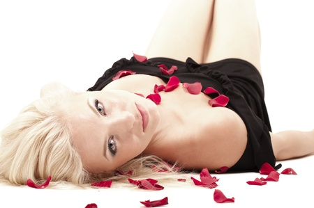 Blonde woman in black dress lying in rose petals isolated on white