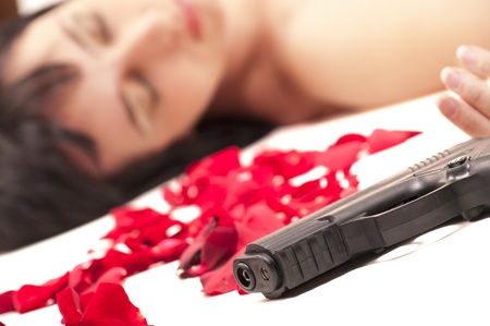 Suicide naked woman lying on the floor with gun and metaphoric blood Stock Photo - 9959394