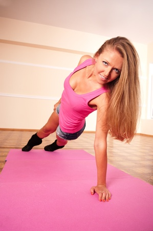 Young woman making flexure exercise in gym in pink top photo