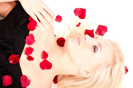 Portrait of beautiful blonde woman in black dress lying in rose petals isolated on white photo