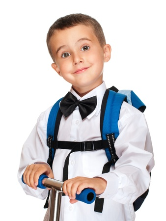 Elementary student boy with backpack and scooter isolated on white photo