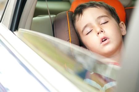 ventana abierta interior: Litle boy duerme en una silla segura en el coche con la ventana abierta