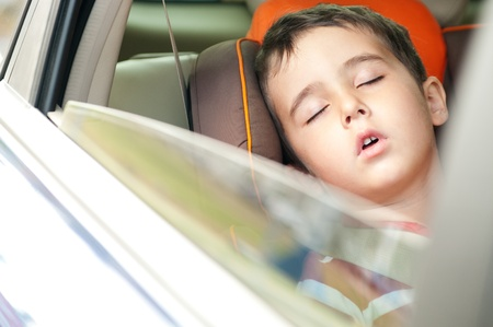 sleeps: Litle boy sleeps in safe chair in car with window open