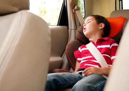 Litle boy sleeps in safe chair in car with window open