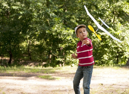 Boy launching toy airplane in summer forest in sunny day