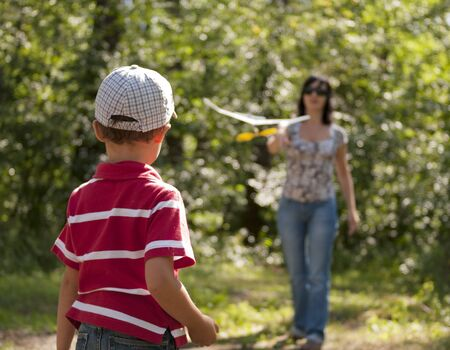 Mother and son launching toy glider outdoors in the forest Stock Photo - 10475415