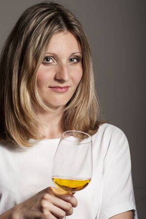 sceptic: Sceptic blonde woman tastes white wine  Stock Photo