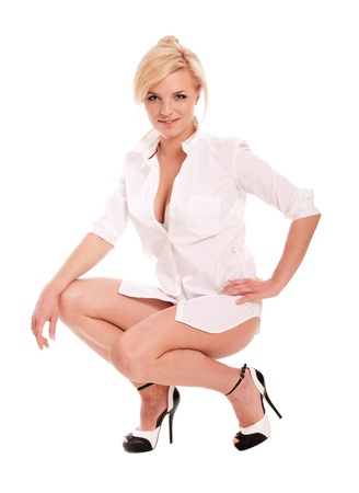 squat: Sexy blonde woman in white shirt on heels isolated on white