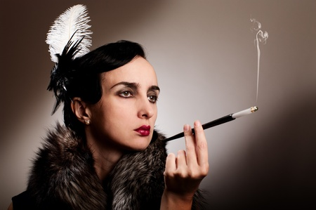 Retro woman in fur and feather with cigarette mouthpiece photo