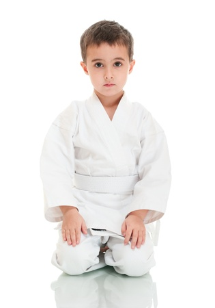 Karate boy sitting in white kimono isolated on white