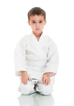Karate boy sitting in white kimono isolated on white photo