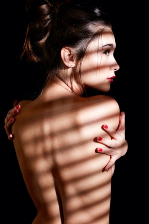 Beautiful young woman with naked back by venetian blinds isolated on black