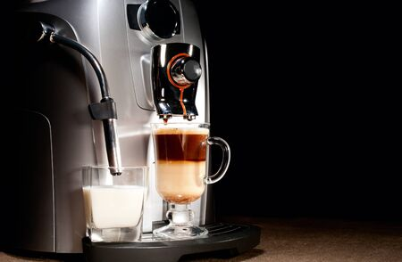 Coffee machine with milk glass and cappuccino on jute