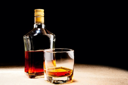 Glass of whisky and bottle on jute