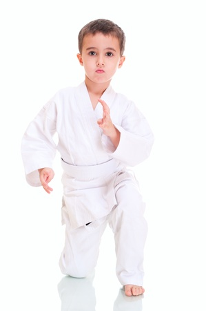 Aikido boy fighting position on a knee in white kimono isolated on white photo