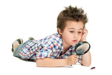 Attentive little boy with weird hair researching the bug using magnifier isolated on white Stock Photo