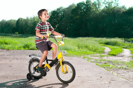 Little boy riding bike on country road outdoors in sunny day