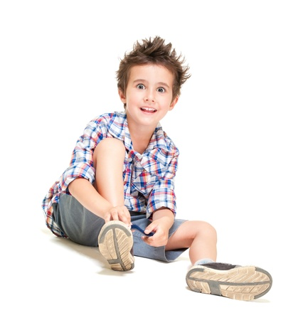 Naughty hairy little boy in shorts and shirt putting on shoes isolated on white