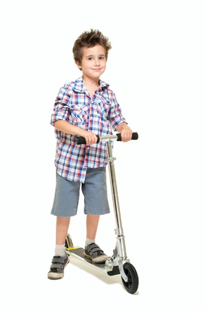 Naughty hairy little boy in shorts and shirt with scooter isolated on white photo
