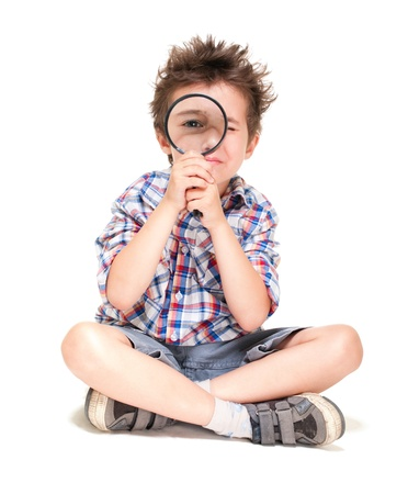 Attentive little boy with weird hair researching using magnifier isolated on white