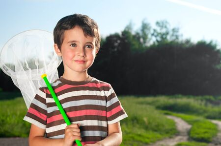 Little boy with hoop net outdoors on the forest meadow in summer photo