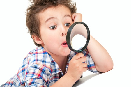 Surprised little boy with weird hair and magnifier isolated on white