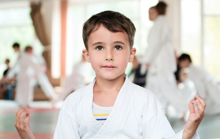 Little boy in kimono meditation before aikido competition in sport hall
