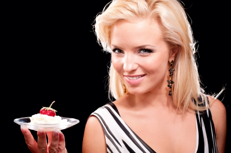 Blonde woman portrait with juicy strawberry in cream isolated on black photo