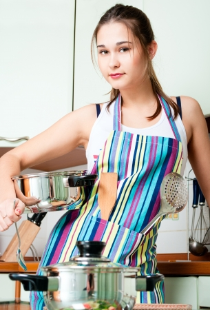 Young housewife on domestic kitchen in apron photo