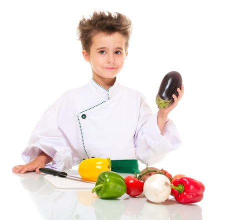 Little happy boy chef in uniform with knife cooking vegatables holding aubergine isolated on white