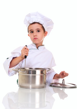 stiring: Little boy chef in uniform with ladle stiring in the pot isolated on white