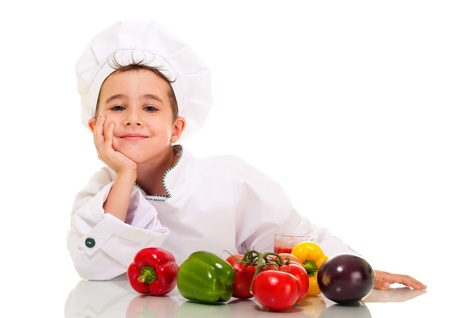 cooking utensils: Little happy boy chef in uniform with vegatables lean on hand isolated on white Stock Photo