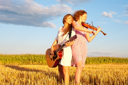 Two young women playing guitar and violin outdoors on the field in summer evening back to back Stock Photo