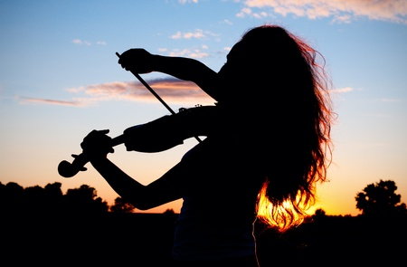 Woman silhouette playing violin in sunset light with hair highlighted Stock Photo