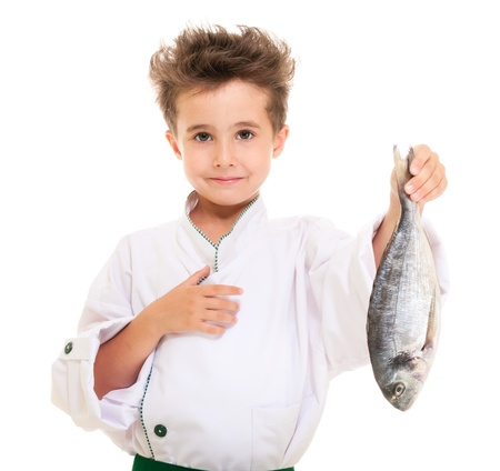 Little boy chef in uniform presenting  dorado fish isolated on white