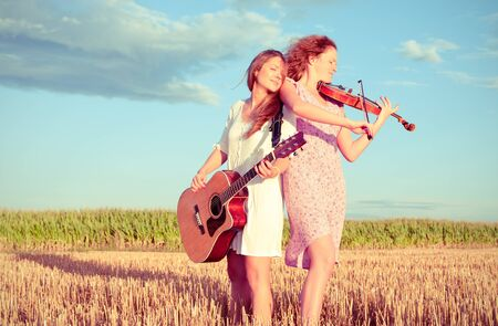 duo: Two young women playing guitar and violin outdoors on the field in summer evening. Split toning.