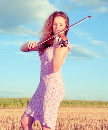 Redhead woman playing violin outdoors on the field in summer evening. Split toning. photo